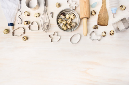 Easter bake tools with quail eggs and biscuit cutter on white wooden background, top view, place for text photo