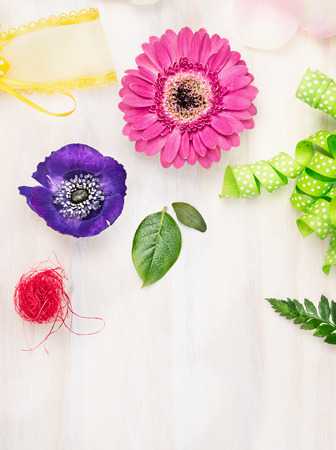 floristry: Floristic background with flowers and accessories on white wooden background, top view, place for text