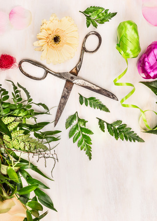 Summer flowers with old scissors and ribbon on white wooden background, top view, place for text photo