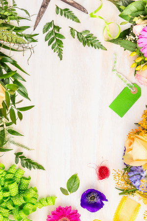 floristic: Bouquet make with summer flowers and Floristic  accessories on white wooden background, top view,place for text