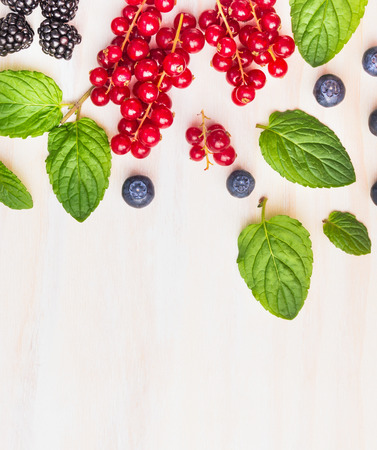 Mint leaves and summer berries on white wooden background, frame, top view, place for text Stock Photo