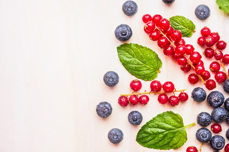 red currants: Red currants, blueberries and blackberries and mint leaves with water drops on white wooden background, top view, place for text