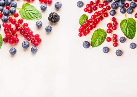 l natural: Fresh organic berries with mint leaves and water drops on white wooden background, top view, place for text