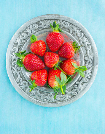 Strawberries served on silver platter, blue background photo
