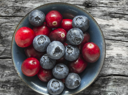 close p: Cranberries and blueberries in blue bowl on old wooden table