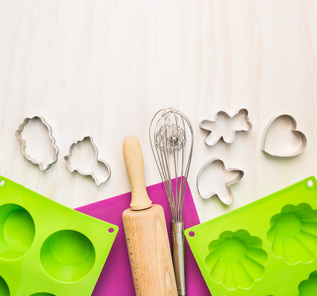 cyst: Bake tools with cake and mold on white wooden background, top view Stock Photo