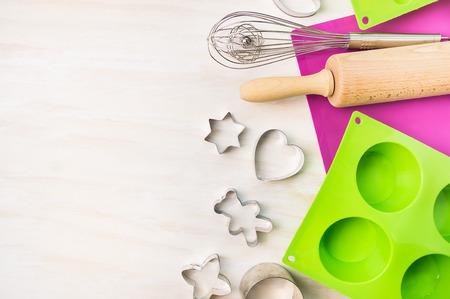 クリスマスのクッキーやケーキを焼く金型マフィンのためのツールと白い木製の背景、上面図、テキストのための場所のカップケーキ