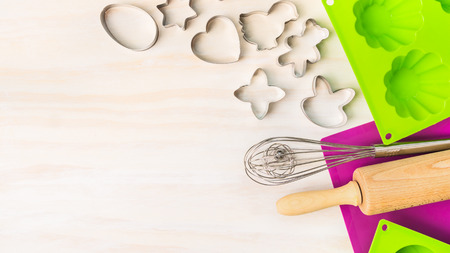 Easter bake tools with cookie cutter, cake mold muffin and cupcake for on white wooden background, top view, place for text