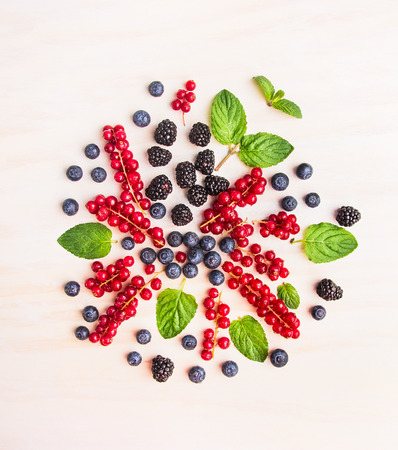 composing: Summer berries and mint leaves composing on white wooden background, top view