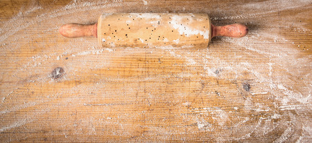 Rolling pin on old wooden background with wheat flour, banner for website, top view photo