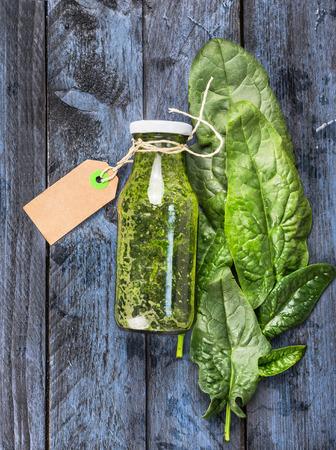 espinaca: Espinaca verde botella batido con la muestra se encuentra en el fondo de madera azul, vista desde arriba Foto de archivo