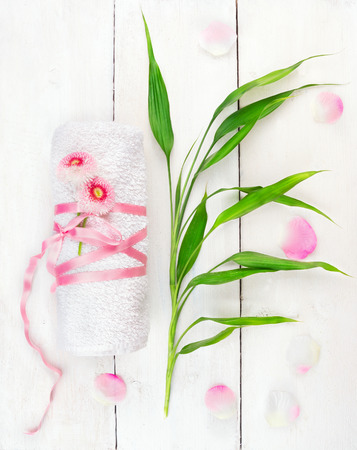 massage table: White rolled up towel with pink flowers and bamboo shoots on white wooden table,spa