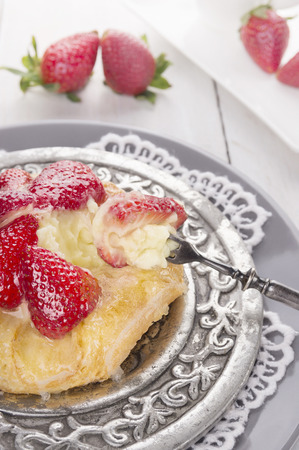 pastry pie with strawberries and custard on silver plate, close up photo
