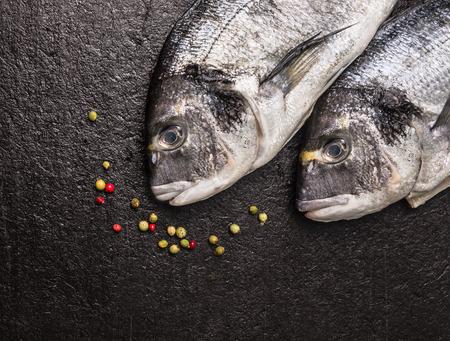 dorado fish: Two raw dorado fish with peppercorn on dark stone background, top view, close up Stock Photo