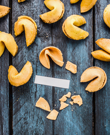 fortune cookie: break fortune cookie with blank paper tag on blue wooden background, top view, coipy space