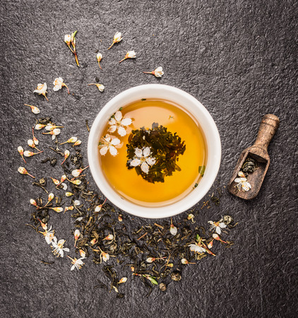 Cup of Jasmine tea, old wooden scoop and fresh flowers on dark stone background, top view