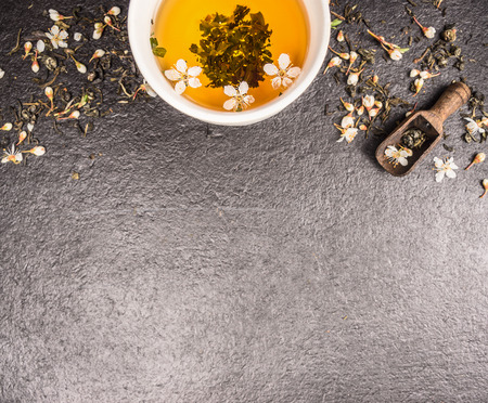 buzzer: Jasmine tea on black stone background with fresh flowers and cup, top view, place for text