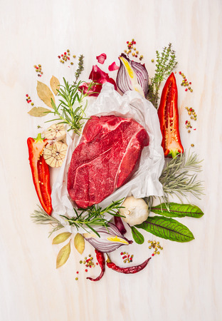 Raw meat, composing with herbs, spices and seasoning on white wooden background, ingredients for cooking, top view