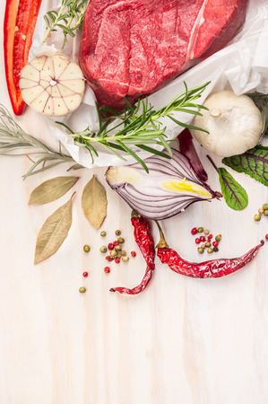 white meat: Raw meat with herbs and spices: bay leaf, garlic, pepper on white wooden background, top view, close up, place for text