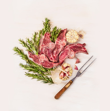 loin chops: Raw lamb loin chops Double with meat fork herb and spices on white wooden background, top view Stock Photo