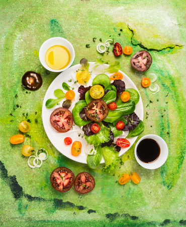 Multicolor Tomatoes salad with oil and vinegar dressing on green background, top view