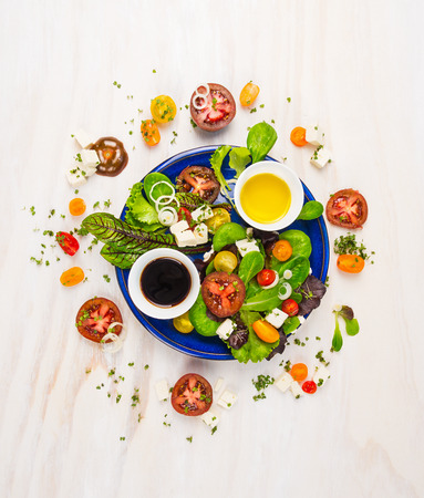 fresh salad with tomatoes, feta cheese, balsamic vinegar and oil in blue plate on white wooden background, top view Stockfoto