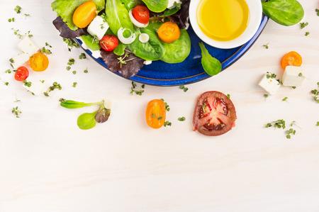 흰색 나무 배경에 파란색 접시에 토마토, 죽은 태아의 치즈와 오일 식초 샐러드, 상위 뷰 프레임