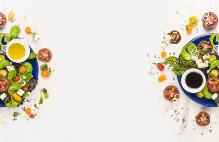 salad with tomatoes, greens, dressing, oil and feta cheese in blue plate on white wooden background, top view, banners for website with cooking concept