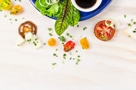 Salad with tomatoes, feta cheese and balsamic vinegar in blue plate on white wooden background, top view frame Stock Photo