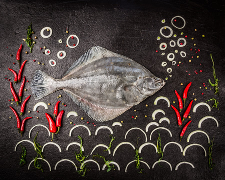 blancos: Raw peces suela entera con especias, algas y la cebolla en el fondo de piedra oscura, vista desde arriba Foto de archivo
