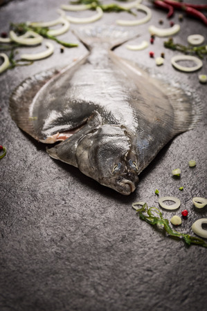 megrim: Raw flounder fish with spices on dark background Stock Photo