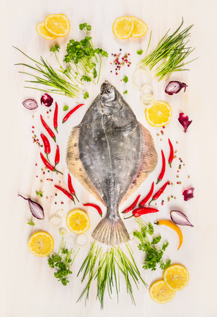 withe: Raw flounder fish with fresh seasoning, lemon and spices on rustic wooden background withe, top view Stock Photo