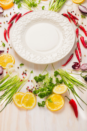 Fresh delicious herbs, spices and seasoning and empty plate on white wooden background photo