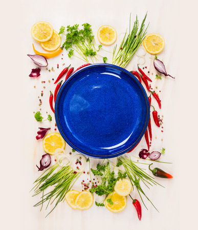 withe: Empty blue plate with fresh seasoning and spices on wooden background withe rustical, top view, place for text Stock Photo