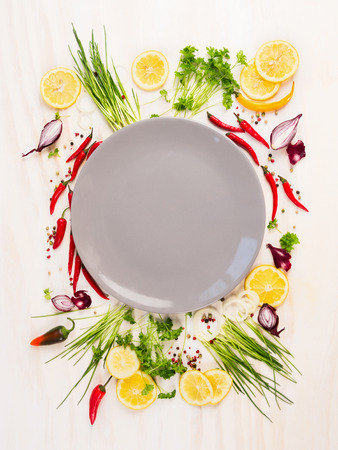 plan view: seasoning and spices around empty gray Plateon white wooden background, top view, copy space Stock Photo