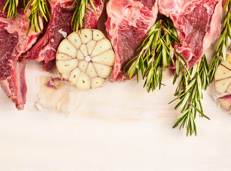 backgound: Raw lamb meat with garlic and rosemary on white wooden backgound, top view, border