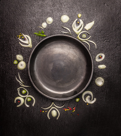 empty black plate with frame of onion slices and spices on dark stone background, top view, copy space Zdjęcie Seryjne