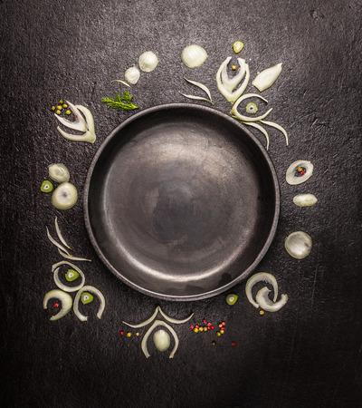 lege zwarte plaat met frame van ui plakjes en specerijen op donkere steen achtergrond, bovenaanzicht, kopieer ruimte
