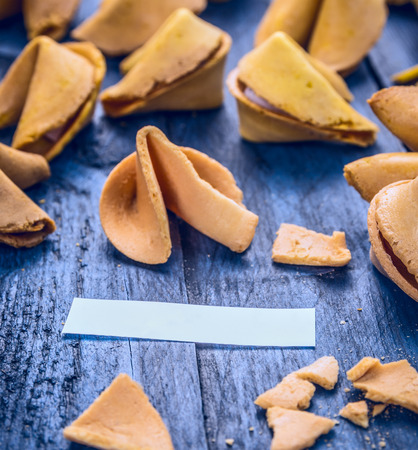 good fortune: cracked open fortune cookie with blank space on blue wooden background, close up
