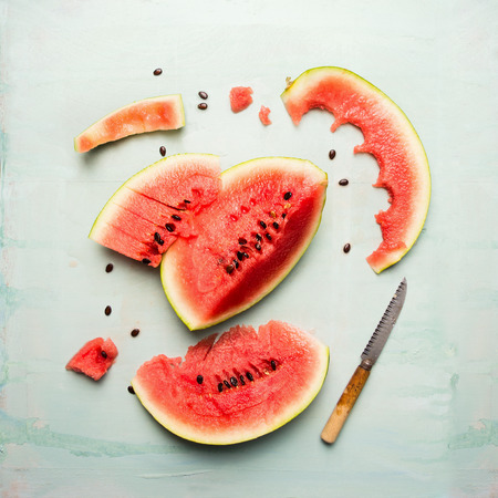 sliced watermelon: watermelon slices with knife on blue wooden background, top view