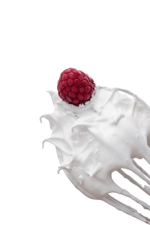 whites: firmly whipped egg whites for meringue on whisk with raspberry Stock Photo