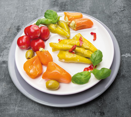 antipasti: Antipasti vegetables peppers with cream cheese hot peppers olives in plate on gray background Stock Photo