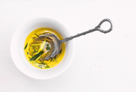 rosemary: Olive Oil with Rosemary in Bowl with antique spoon on white wooden table
