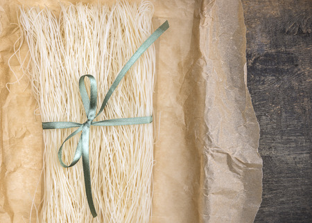 rice paper: Chinese rice noodles dry in crumpled paper packaging with green ribbon