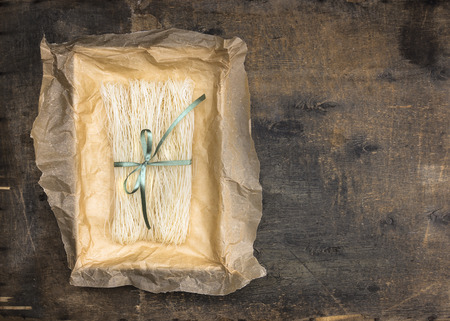 rice paper: Chinese rice noodles in crumpled paper packaging with green ribbon on an old wooden table