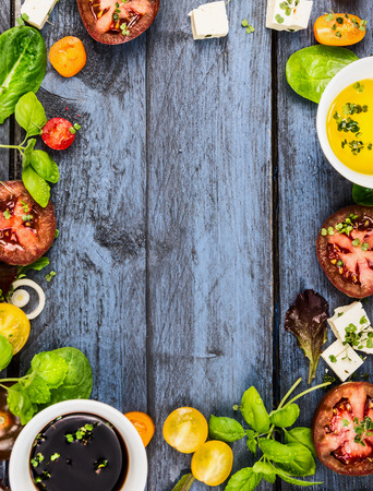 Salad making food frame with oilvinegar tomatoes basil and cheese on blue rustic wooden background top view vertical Foto de archivo