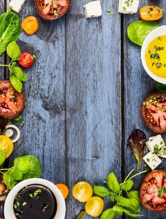 Sallad gör mat ram med oilvinegar tomater basilika och ost på blå rustikt trä bakgrund uppifrån vertikal