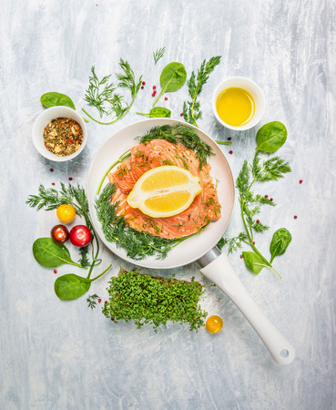raw salmon in white pan with lemon and fresh herbs top view photo