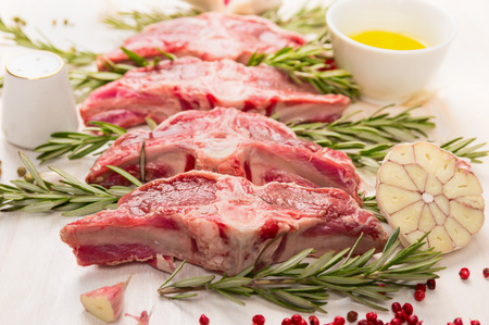 Raw fresh lamb with rosemary and garlic on white wooden background close up photo