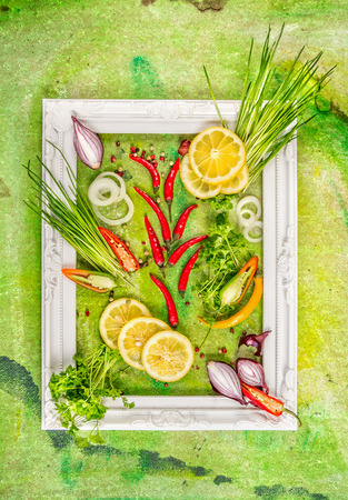 yellow art: white frame with chives, spices and lemon slice, composing on green background, top view